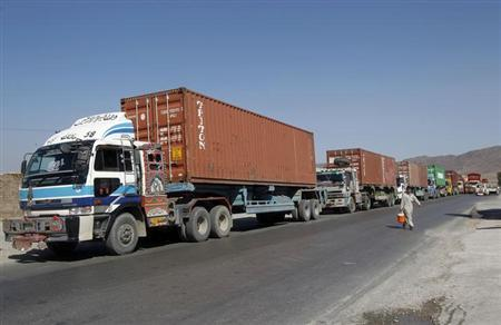 Trucks carrying supplies for NATO troops cross into Afghanistan from Pakistan at the Tor kham July 28, 2012.REUTERS/Parwiz/Files