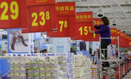 A worker adjusts a price tag at a supermarket in Wuhan, Hubei province, November 9, 2012. REUTERS/Stringer