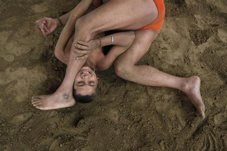 Wrestlers fight at a permanent mud wrestling ring at ''Sia Ram bhajan samati akhaara'', a traditional Indian wrestling training centre, on the banks of the river Ganges in Kolkata February 17, 2013. REUTERS/Rupak De Chowdhuri/Files