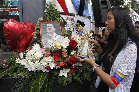 A woman places a replica figurine of the Virgen de Lujan during a rally honouring late Venezuelan President Hugo Chavez outside the Venezuela's Embassy in Buenos Aires March 9, 2013. REUTERS/Enrique Marcarian