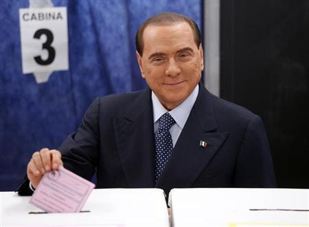 Former Prime Minister Silvio Berlusconi casts his vote at a polling station in Milan February 24, 2013. REUTERS/Stefano Rellandini