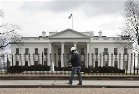 A worker cleans a sidewalk outside the White House in Washington March 2, 2013. REUTERS/Yuri Gripas