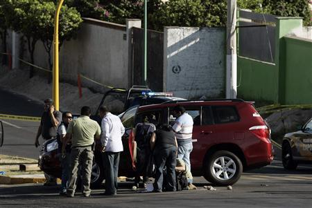 Investigators and members of a forensic team gather around a car where the new tourism minister of Jalisco state Jose de Jesus Gallegos was shot dead at a crime scene between Guadalajara and Zapopan limits March 9, 2013. REUTERS/Alejandro Acosta