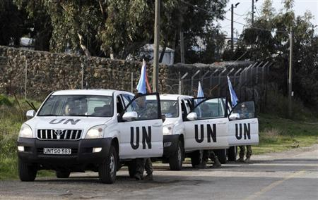 United Nations peacekeepers put on protective gear before driving through the Kuneitra border crossing between Israel and Syria, in the Israeli occupied Golan Heights March 8, 2013. REUTERS/Baz Ratner