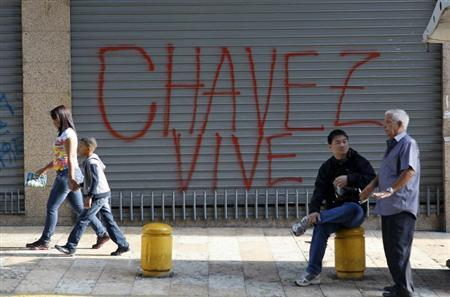 Residents are seen near a graffitti that reads, ''Chavez is alive'' along a street in Caracas March 9, 2013. REUTERS/Mariana Bazo