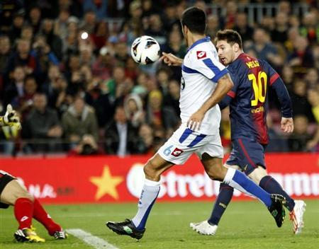 Barcelona's Lionel Messi (R) scores his goal against Deportivo's Aythami (C) and goalkeeper Aranzubia (L) during their Spanish first division match at Nou Camp stadium in Barcelona March 9, 2013. REUTERS/Gustau Nacarino