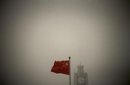 A Chinese national flag flies in front of Beijing Telegraph Building on a hazy morning in central Beijing, February 28, 2013. REUTERS/Petar Kujundzic