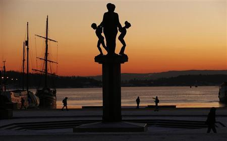 People walk by the harbour at sunset in Oslo December 11, 2012. REUTERS/Suzanne Plunkett