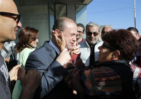 Labour Party leader Joseph Muscat (C) and his wife Michelle (2nd L) are greeted by supporters as they arrive to vote at a polling station in their hometown of Burmarrad, outside Valletta, March 9, 2013. REUTERS/Darrin Zammit Lupi