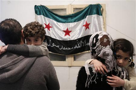 Syrian refugee Osama (L), 35, and his wife, pose with their two children in front of a Syrian opposition flag inside their home in Athens February 7, 2013. REUTERS/John Kolesidis