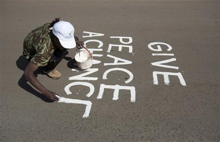 An artist known as solo7 paints a peace message on the tarmac in the Kibera slum in the Kenyan capital of Nairobi March 9, 2013. REUTERS/Karel Prinsloo