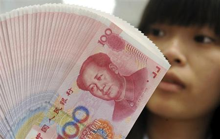 An employee counts Chinese yuan notes inside a bank in Taipei February 6, 2013. REUTERS/Stringer