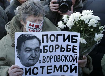 A woman holds a placard with a portrait of Sergei Magnitsky during an unauthorised rally in central Moscow December 15, 2012.. REUTERS/Tatyana Makeyeva