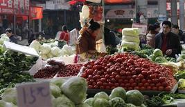 A vendor selling vegetables waits for customers at a market in Beijing February 27, 2013. REUTERS/Stringer