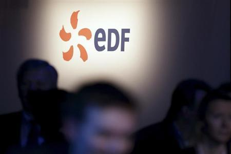 People walk past the logo of French state-owned utility EDF during the company's 2012 annual result presentation in Paris February 14, 2013. REUTERS/Philippe Wojazer