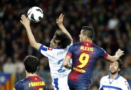 Barcelona's Alexis Sanchez (L) and Cesc Fabregas (R) look at Deportivo's Juan Valeron handling the ball during their Spanish first division soccer match at Nou Camp stadium in Barcelona March 9, 2013.   REUTERS/Gustau Nacarino