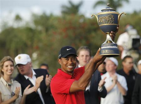 Tiger Woods hoists the Gene Sarazen Trophy after winning the 2013 WGC-Cadillac Championship PGA golf tournament in Doral, Florida March 10, 2013. REUTERS/Andrew Innerarity