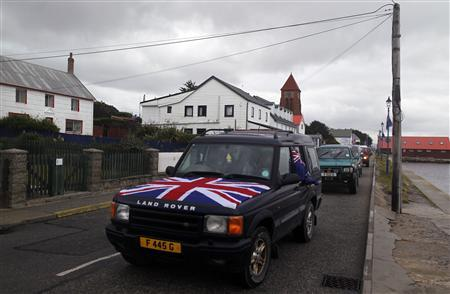 People drive their cars on Ross road with Union Jack and Falkland Islands flags during a parade in Stanley March 10, 2013. REUTERS/Marcos Brindicci