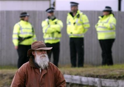 Falkland islander Phil Middleton walks past police officers in Stanley March 10, 2013. Residents of the Falkland Islands started voting on Sunday in a sovereignty referendum that seeks to counter Argentina's increasingly assertive claim over the British-ruled territory. REUTERS/Marcos Brindicci