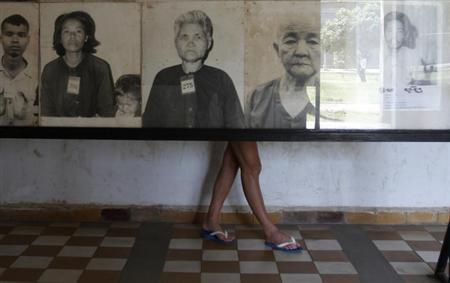A tourist looks at portraits of victims killed in the former Khmer Rouge regime's S-21 security prison, presently known as Tuol Sleng Genocide Museum, in Phnom Penh March 5, 2013. REUTERS/Samrang Pring