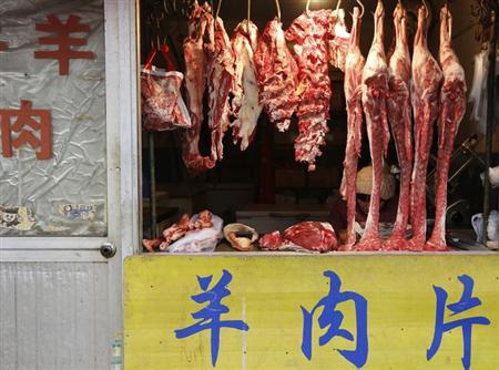 A vendor reads as she waits for customers inside a butcher shop at a market in Beijing, February 25, 2013. REUTERS/Kim Kyung-Hoon/Files