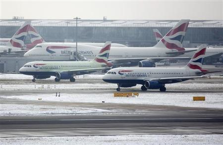 British Airways aircraft taxi after snowfall at Heathrow airport in London January 21, 2013. REUTERS/Neil Hall