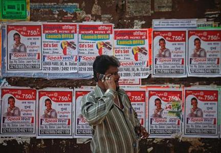 A man speaks on his mobile phone as he waits to cross a street in Mumbai February 6, 2012. REUTERS/Danish Siddiqui/Files