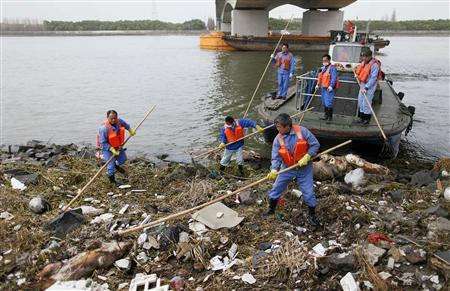 Cleaning workers retrieve the carcasses of pigs from a branch of Huangpu River in Shanghai, March 10, 2013. Over 2,200 pigs have been found dead in one of Shanghai's main water sources, official media reported on March 11, 2013, triggering a public outcry in China where concerns over food safety and environmental pollution run high. Picture taken March 10, 2013. REUTERS/Stringer