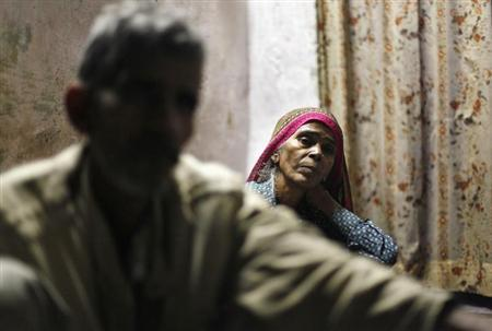 Mange Lal Singh (L) and Ram Bai (R), father and mother of Ram Singh, the driver of the bus in which a young woman was gang-raped and fatally injured three months ago, sit inside their house at Ravi Das camp in New Delhi March 11, 2013. REUTERS/Mansi Thapliyal