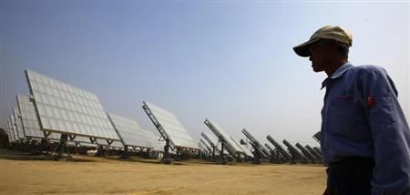 A worker walks past panels at a high-concentration photovoltaic (HCPV) solar energy power plant in Lujhu Township of Kaohsiung County, southern Taiwan, January 22, 2010. REUTERS/Nicky Loh