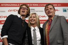 "Actress Olivia Newton John (C) smiles as she poses with director Stephan Elliot (R) and actor Kris Marshall during a photocall of their movie ""A Few Best Men"" at the Rome Film Festival October 28, 2011. REUTERS/Alessandro Bianchi"