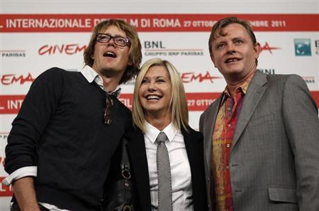 Actress Olivia Newton John (C) smiles as she poses with director Stephan Elliot (R) and actor Kris Marshall during a photocall of their movie ''A Few Best Men'' at the Rome Film Festival October 28, 2011. REUTERS/Alessandro Bianchi