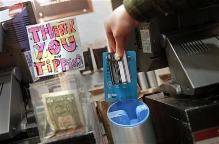 A man demonstrates the use of a DipJar, an electronic version of the tip jar found in coffee shops, on the counter of an Oren's Daily Roast in New York February 13, 2013. REUTERS/Carlo Allegri