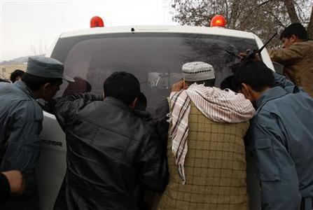 Afghans look at the bodies of Afghan policemen inside an ambulance after they were killed in Wardak province, March 11, 2013. Two American soldiers were killed in a so-called insider attack when a person in an Afghan military uniform turned his weapon on U.S. and Afghan forces at a joint base in the restive east of the country, coalition forces said on Monday. REUTERS/ Mohammad Ishaq