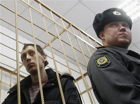 Pavel Dmitrichenko (L) looks out from the defendant's holding cell during a court hearing in Moscow March 7, 2013. REUTERS/Maxim Shemetov