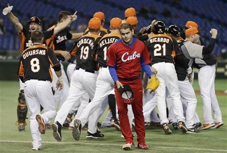 Cuba's pitcher Diosdany Castillo (C) walks off the field as Netherlands' players celebrate after defeating Cuba at the World Baseball Classic (WBC) second round game in Tokyo March 11, 2013. REUTERS/Toru Hanai