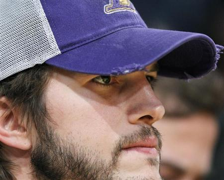 Actor Ashton Kutcher wears a worn Lakers cap as he sits courtside watching the Los Angeles Lakers play the Oklahoma City Thunder during Game 4 of their NBA Western Conference semi-final playoff basketball game in Los Angeles, California May 19, 2012. REUTERS/Lucy Nicholson/Files