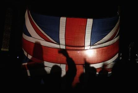 Falkland islanders are silhouetted behind the Union Jack as they react after hearing the results of the referendum in Stanley March 11, 2013. REUTERS/Marcos Brindicci