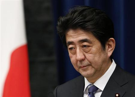 Japan's Prime Minister Shinzo Abe attends a news conference next to the national flag, which is hung with a black ribbon as a symbol of mourning for victims of the March 11, 2011 earthquake and tsunami, at his official residence in Tokyo March 11, 2013. REUTERS/Yuya Shino