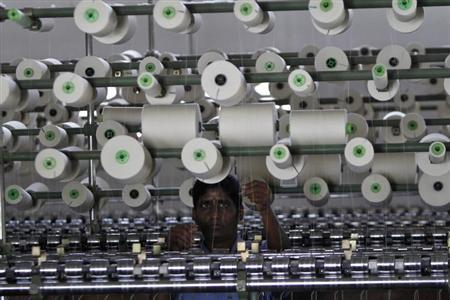 A worker tends to yarn-spinning equipment at a factory in Coimbatore, about 500 km (310 miles) from Chennai, January 8, 2013. REUTERS/Babu/Files