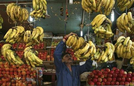 A fruit seller arranges bananas at his stall along a road in Jammu November 3, 2011. REUTERS/Mukesh Gupta/Files