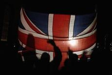 Жители Фолклендских островов стоят за флагом Великобритании во время объявления результатов референдума в Стэнли 11 марта 2013 года. Жители Фолклендских островов, которые Аргентина в 1980-х пыталась отвоевать у Великобритании, практически единогласно проголосовали за сохранение британского суверенитета над архипелагом. REUTERS/Marcos Brindicci