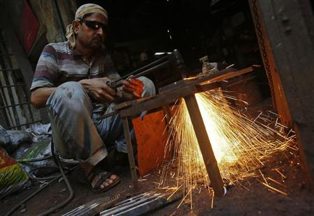 A labourer works outside an aluminium smelting factory in Mumbai March 12, 2013. REUTERS/Vivek Prakash