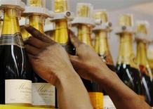 A Morrisons supermarket worker arranges champagne bottle at a store in London November 21, 2012. REUTERS/Luke MacGregor