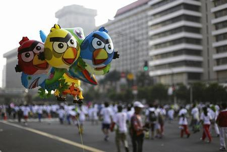 Angry Birds balloons are seen as people run during Car Free Day at the main street in Jakarta July 8, 2012. REUTERS/Beawiharta/Files