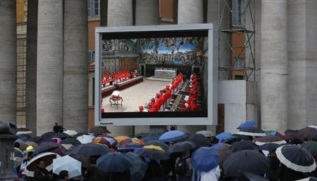 People in Saint Peter's Square watch a live television screen showing cardinals entering the Sistine Chapel to begin the conclave in order to elect a successor to Pope Benedict, at the Vatican March 12, 2013. REUTERS/Stefano Rellandini