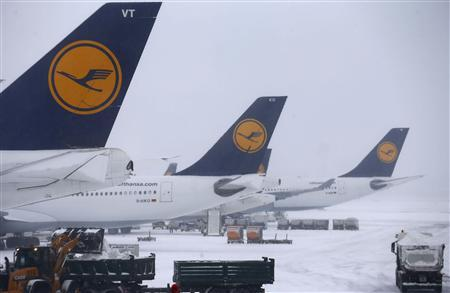 Heavy equipment is used to clear the tarmac from snow at the Fraport airport in Frankfurt, March 12 2013. The airport was closed due to heavy snowfalls and hundreds of flights were cancelled on thursday. Picture is taken through a window. REUTERS/Kai Pfaffenbach