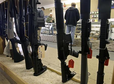 Customers are seen shopping for handguns through a rack of assault rifles at the Guns-R-Us gun shop in Phoenix, Arizona, December 20, 2012. REUTERS/Ralph D. Freso