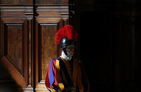 A Swiss Guard is seen during a mass in St. Peter's Basilica at the Vatican March 12, 2013. All cardinals, including those over 80 who will not vote in the conclave, celebrate Mass in St Peter's Basilica to pray for the election of the new pope. The Mass is called 'Pro Eligendo Romano Pontefice' ('For the Election of the Roman Pontiff') and is open to the public. REUTERS-Stefano Rellandini