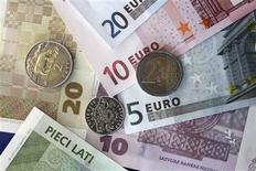 Monnaie lettone et billets en euros. La Lettonie, qui a présenté la semaine dernière sa candidature à l'entrée dans la zone euro, serait le pays le plus pauvre de la région si elle l'intégrait mais elle dispose d'une économie suffisamment solide pour respecter les critères imposés par l'Union européenne (UE). /Photo prise le 9 mars 2013/REUTERS/Ints Kalnins